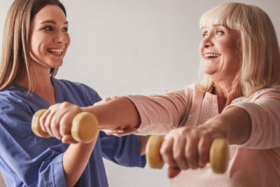 caregiver helping senior woman with her exercise